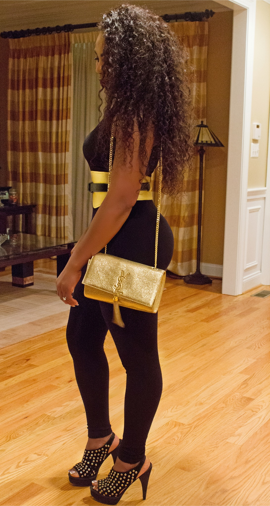 Thelma Okoro wearing Yves Saint Laurent Gold Clutch and Belt side view